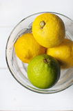 Fresh lemons in glass bowl. Fresh lemons and lime in glass bowl on white table Stock Images