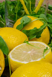 Fresh lemons with green salad leaves close up Stock Images
