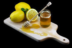 Fresh lemons and honey on wooden board Royalty Free Stock Images