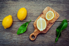 Fresh lemons and  lemons leaves on rustic wooden background. Fre Royalty Free Stock Photos