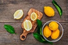 Fresh lemons and  lemons leaves on rustic wooden background. Fre Stock Photography