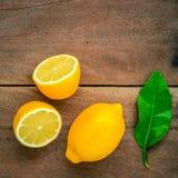 Fresh lemons and  lemons leaves on rustic wooden background. Fre Stock Photo