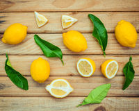Fresh lemons and  lemons leaves on rustic wooden background. Fre Royalty Free Stock Photo