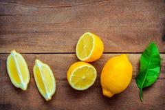 Fresh lemons and  lemons leaves on rustic wooden background. Fre Stock Images