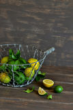 Fresh lemons and limes in a vintage basket Royalty Free Stock Photos