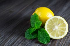 Fresh lemons and mint leaves on a dark wooden background royalty free stock photo