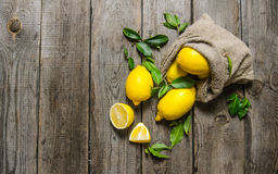 Fresh lemons into an old bag with leaves. Royalty Free Stock Images