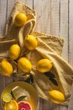 Fresh lemons with tablecloth. On wooden tabletop Royalty Free Stock Photo