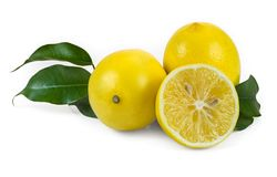 Fresh lemons. Two and a half fresh lemons with leaves on a white background Stock Images