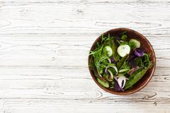 Fresh lettuce, arugula, frisee, basil, cucumber and onions salad royalty free stock photo