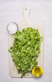 Fresh lettuce on a cutting board with salt and oil wooden rustic background top view close up Royalty Free Stock Photos