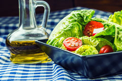 Fresh lettuce salad with cherry tomatoes radish and carafe with olive oil on wooden table. Royalty Free Stock Images