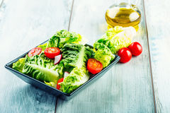 Fresh lettuce salad with cherry tomatoes radish and carafe with olive oil on wooden table. Stock Photo