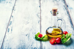 Fresh lettuce salad with cherry tomatoes radish and carafe with olive oil on wooden table. Several ingredients of Mediterranean cuisine Royalty Free Stock Photography