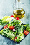 Fresh lettuce salad with cherry tomatoes radish and carafe with olive oil on wooden table. Several ingredients of Mediterranean cu Royalty Free Stock Photo
