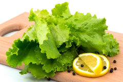 Fresh lettuce with slices of lemon and black pepper on the cutti Stock Photo