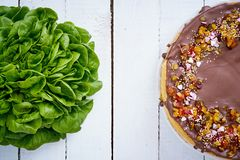 Fresh lettuce and sweet caloric cake on an old white wooden table. Fresh green lettuce and sweet caloric cake on an old white wooden table stock image