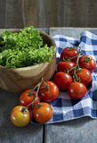 Fresh lettuce and various tomato. Fresh garden salad in a wooden bowl and tomato stock photography