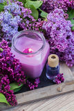 Fresh lilac flowers with candle. Fresh violet lilac flowers with candle and aromaric oil Stock Photos
