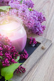 Fresh lilac flowers with candle. Fresh violet lilac flowers with burning candle Royalty Free Stock Image