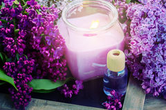 Fresh lilac flowers spa setting with candle. Fresh purple lilac flowers with burning candle Royalty Free Stock Photo