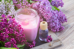 Fresh lilac flowers spa setting with candle. Fresh violet lilac flowers with burning candle Royalty Free Stock Photos