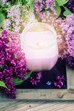 Fresh lilac flowers spa setting. Fresh purple  lilac flowers with burning candle Royalty Free Stock Photos