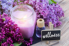Fresh lilac flowers spa setting. Purple lilac flowers with candle, aromaric oil and  tag with wellness word Stock Photo