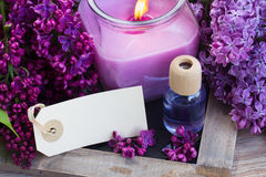 Fresh lilac flowers spa setting. Fresh violet lilac flowers with candle, aromaric oil and empty tag Stock Photos