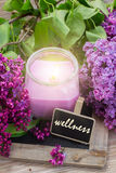 Fresh lilac flowers spa setting. Fresh violet lilac flowers with candle, aromaric oil and  tag with wellness word Royalty Free Stock Images
