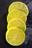 Fresh lima slices with water drops on black Royalty Free Stock Photography