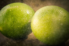 Fresh lime close up with drops of water on woden background. Royalty Free Stock Photography