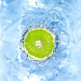 Fresh lime dropped into water. With bubbles isolated on white Stock Images