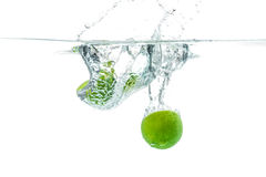 Fresh lime dropped into the water with water splash on a white b Royalty Free Stock Images