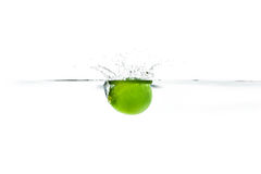 Fresh lime dropped into the water with water splash on a white b Stock Images