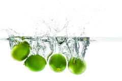 Fresh lime dropped into the water with water splash on a white b Royalty Free Stock Image