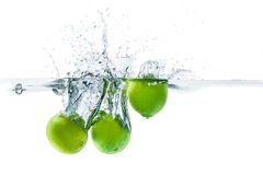 Fresh lime dropped into the water with water splash on a white b Stock Photography