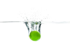 Fresh lime dropped into the water with water splash on a white b Royalty Free Stock Photography