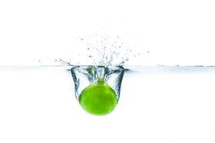 Fresh lime dropped into the water with water splash on a white b. Ackground Stock Images