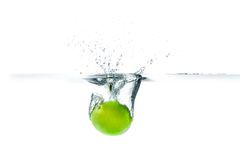 Fresh lime dropped into the water with water splash on a white b Stock Image