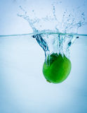Fresh lime falling into water, on white Stock Photo
