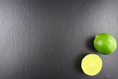 Fresh lime fruit on a slate plate food background texture Stock Image
