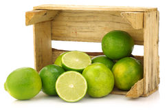 Fresh lime fruit in a wooden crate. On a white background Stock Photos