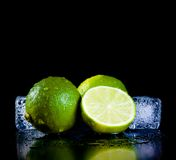 Fresh lime with ice cubes with space for text. Fresh lime with ice cubes on black background with space for text Royalty Free Stock Image
