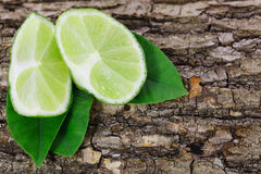 Fresh lime with leaf on a bark of tree background Stock Photos