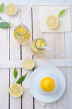 Fresh lime and lemon, squeezer and two glasses of lemonade on the table Royalty Free Stock Photo