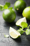 Fresh lime and mint on the black table. Selective focus Royalty Free Stock Images