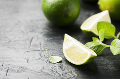 Fresh lime and mint on the black table. Selective focus Stock Image