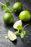 Fresh lime and mint on the black table. Selective focus Stock Photos