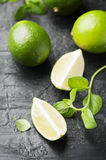 Fresh lime and mint on the black table. Selective focus Royalty Free Stock Photos